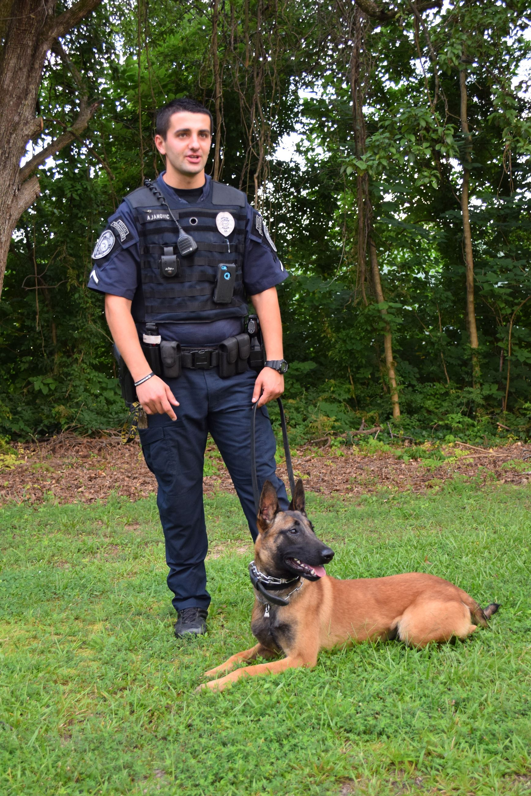 Officer Ajanovic standing with Ajax, the police dog